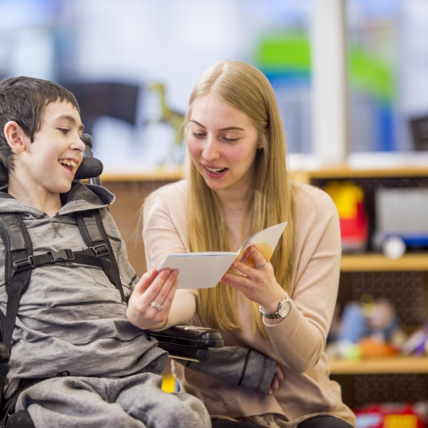 Lady reading to disabled boy